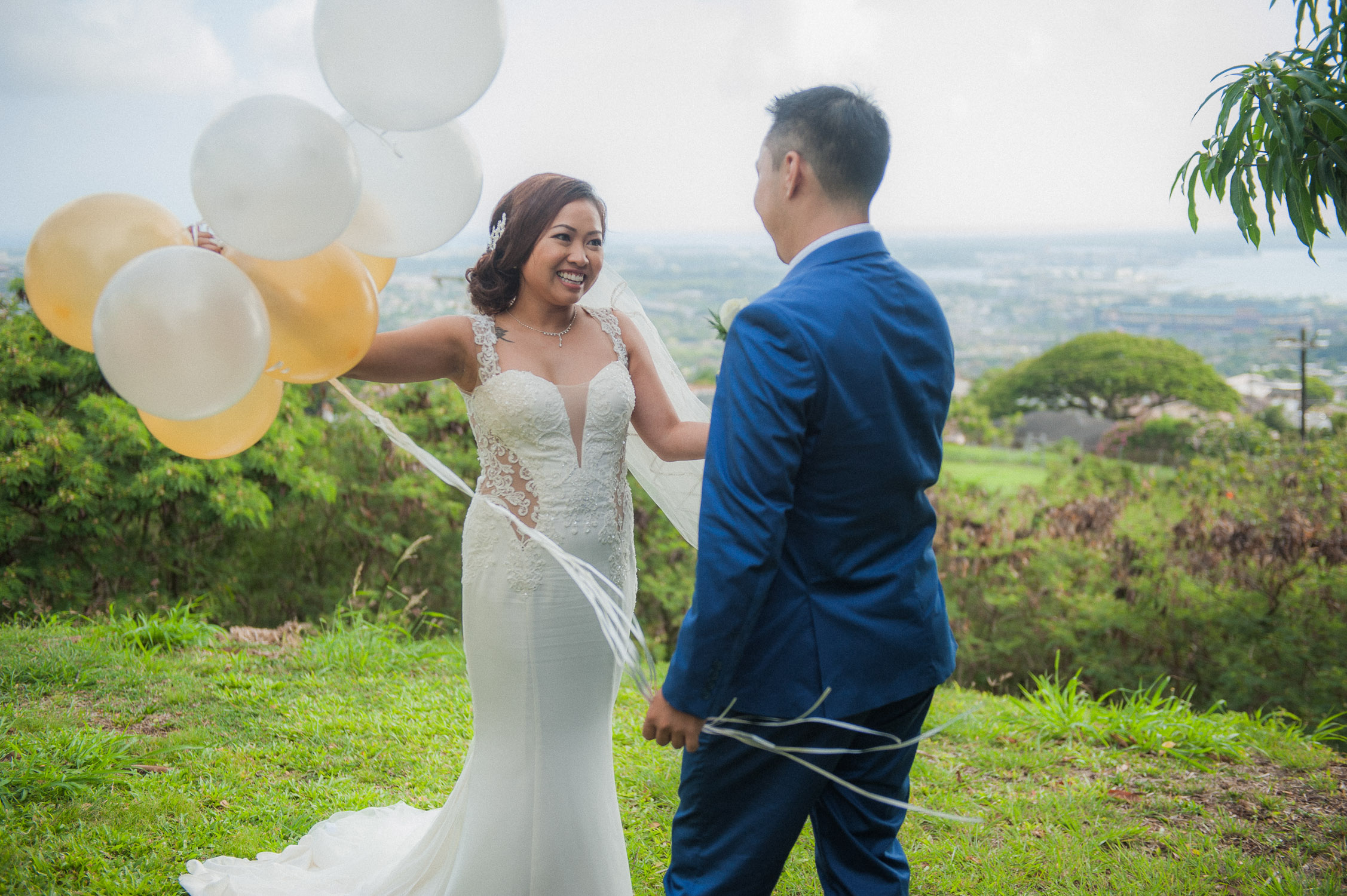 Groom seeing bride for first time with white and gold balloons