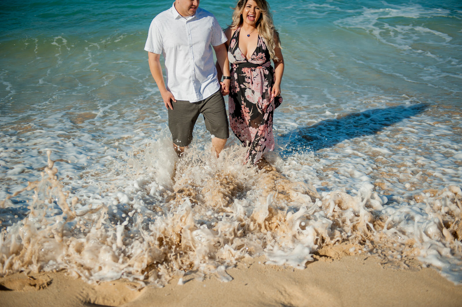 Couple getting splashed by wave