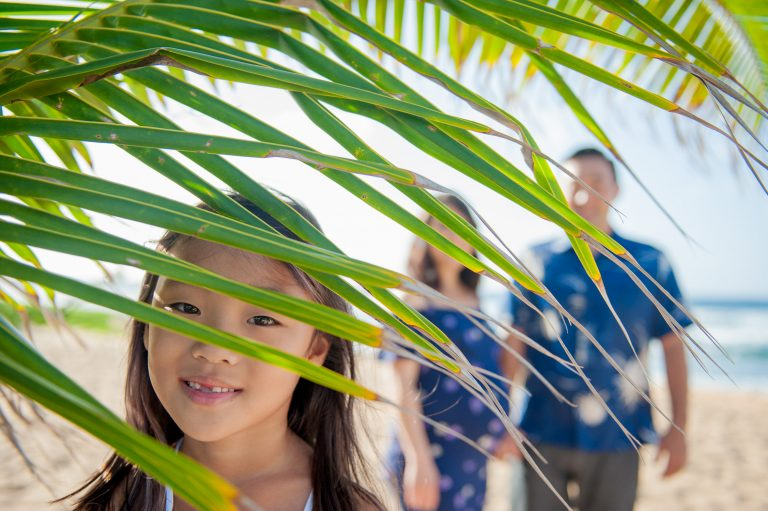Girl peeking through palm leaves with parents in background