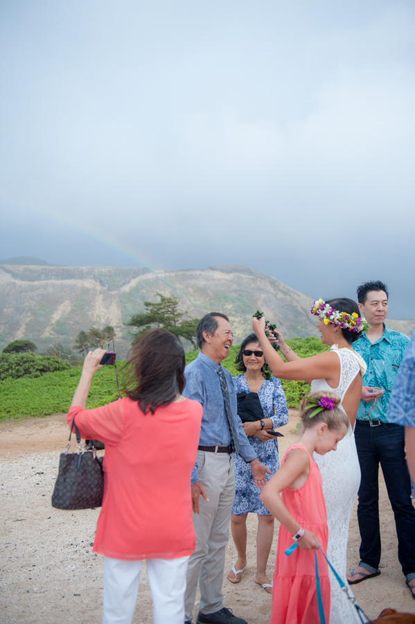 bride giving dad a lei with rainbow in background