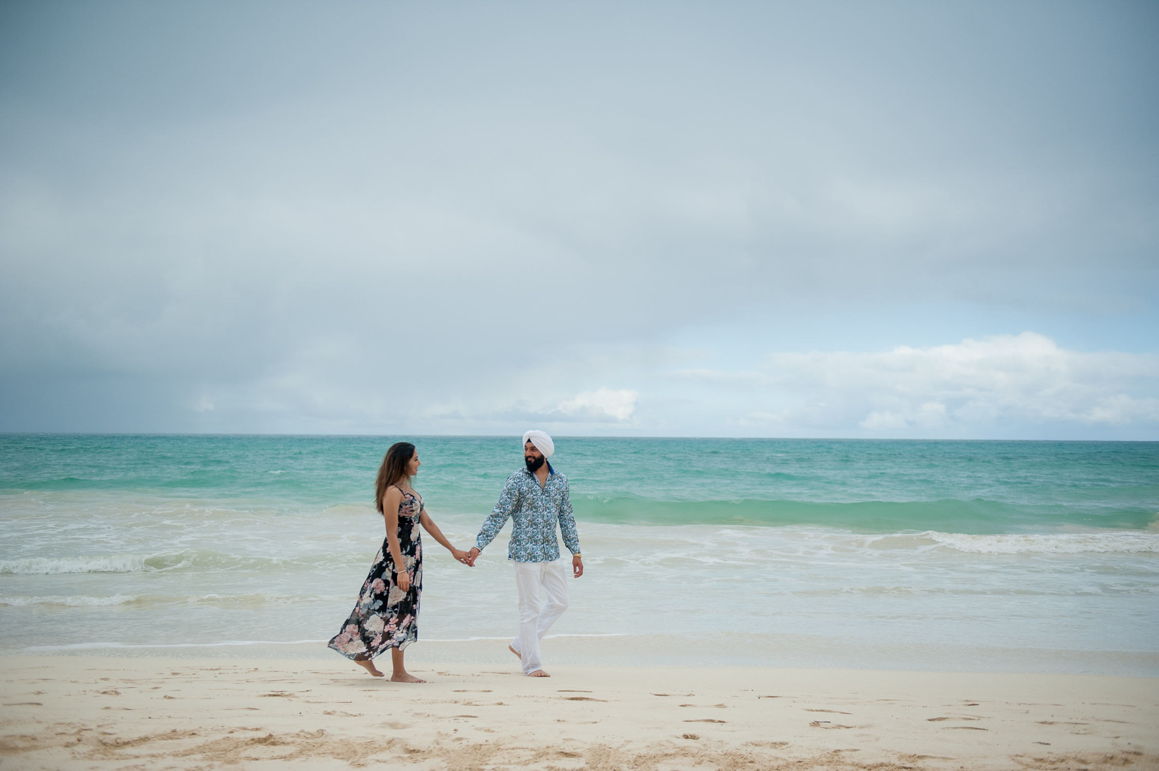 Newly engaged couple walking down Waimanalo Beach
