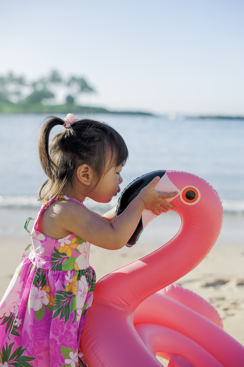 Small girl kissing pink flamingo floatie
