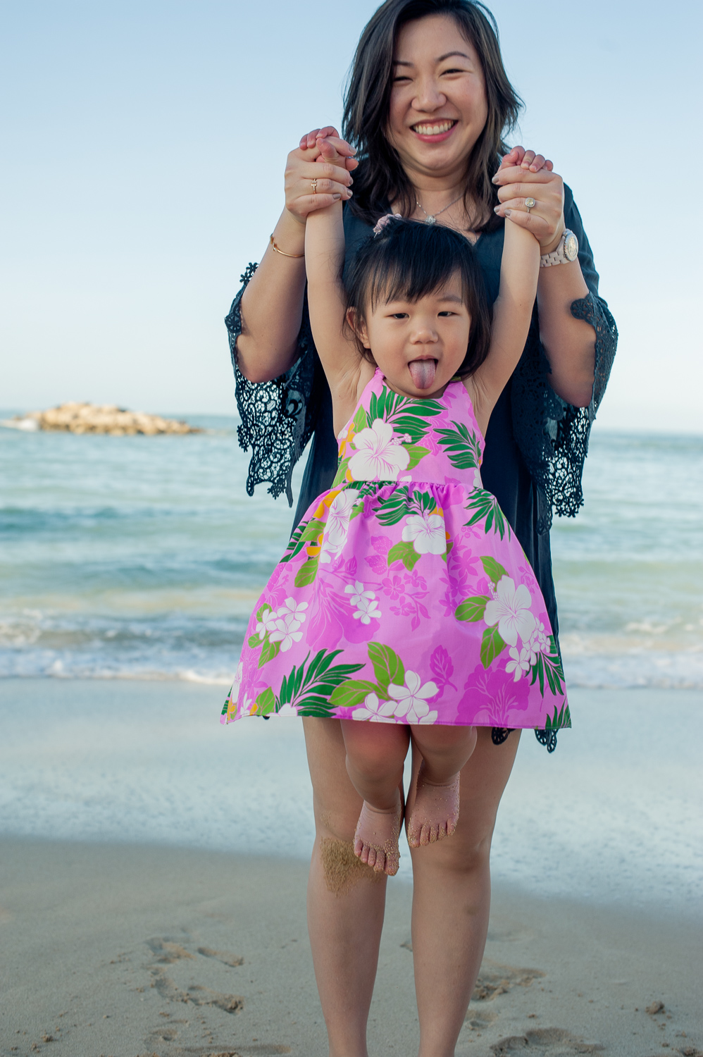 Mom holding daughter with pink aloha dress