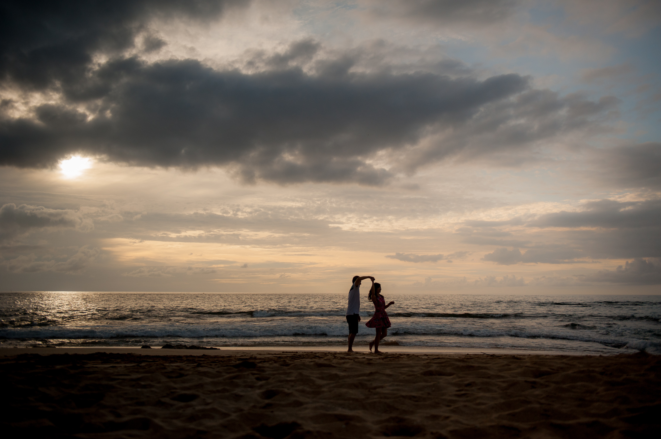 Far away shot of couple dancing on North Shore beach with dark and orange clouds