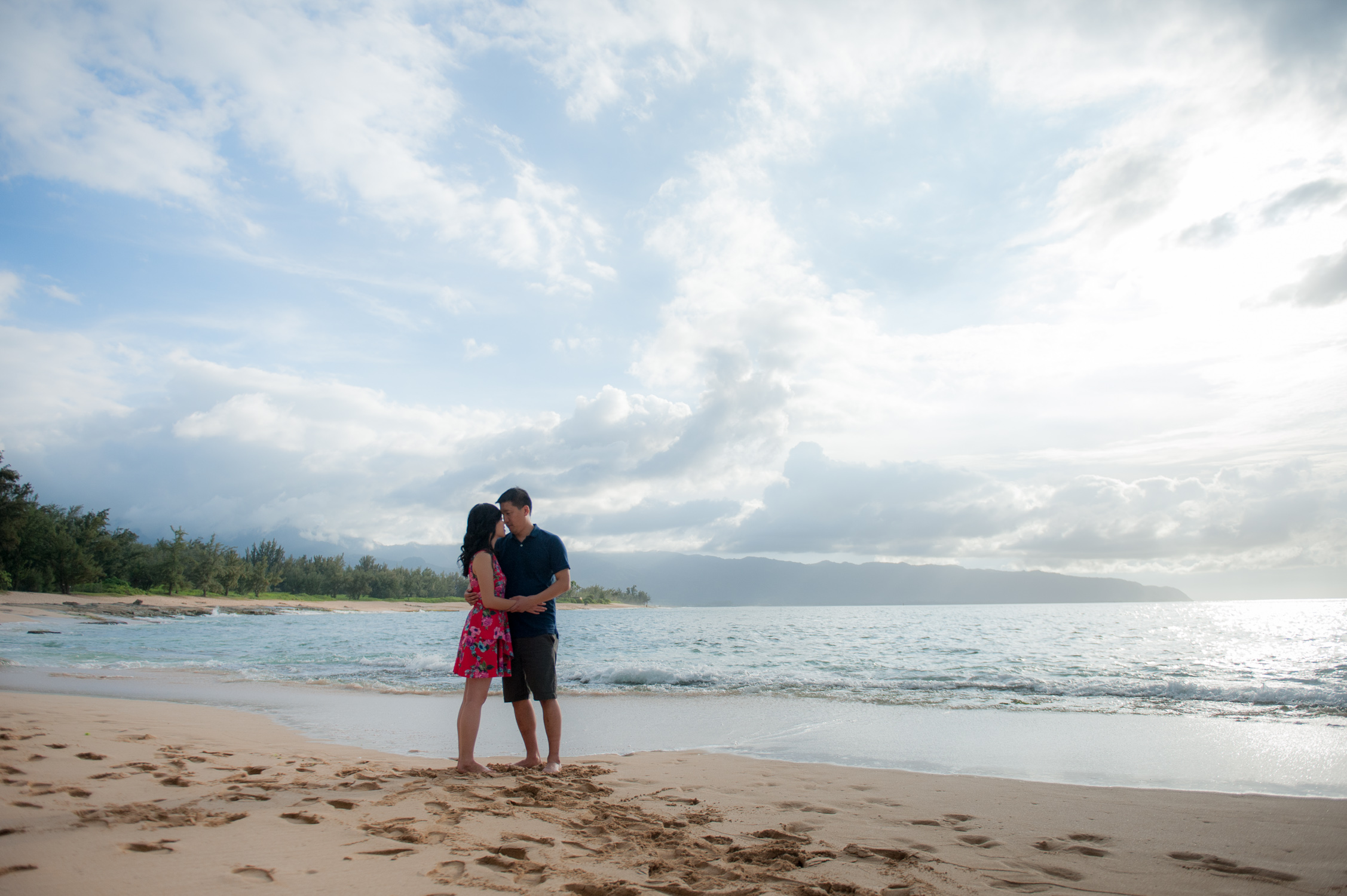 Far away shot of couple with clouds and island in backdrop