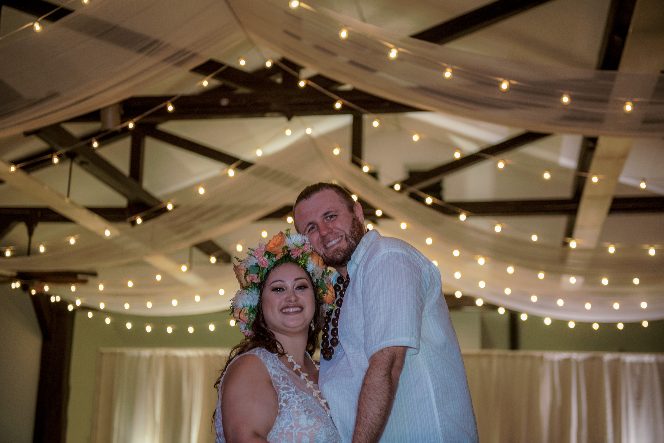 Bridal couple dancing with strung up lights