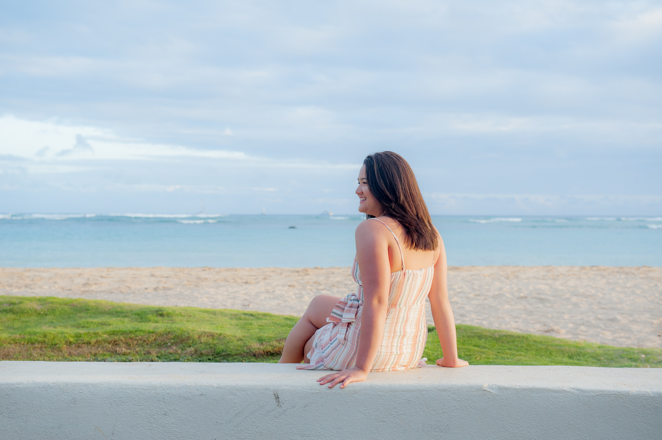 Senior girl sitting on wall at ala moana beach park