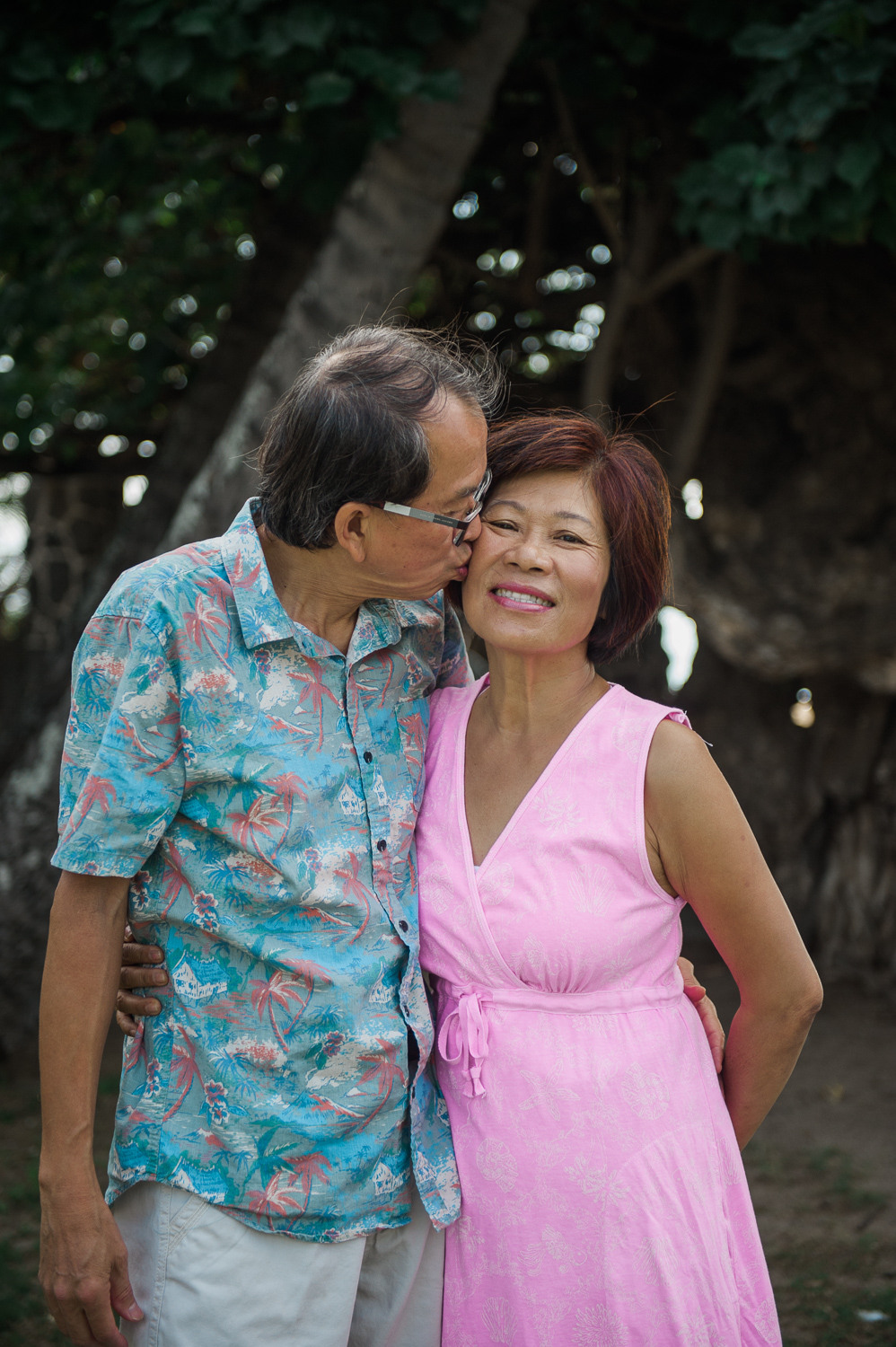 Man in blue shirt kissing wife in pink dress