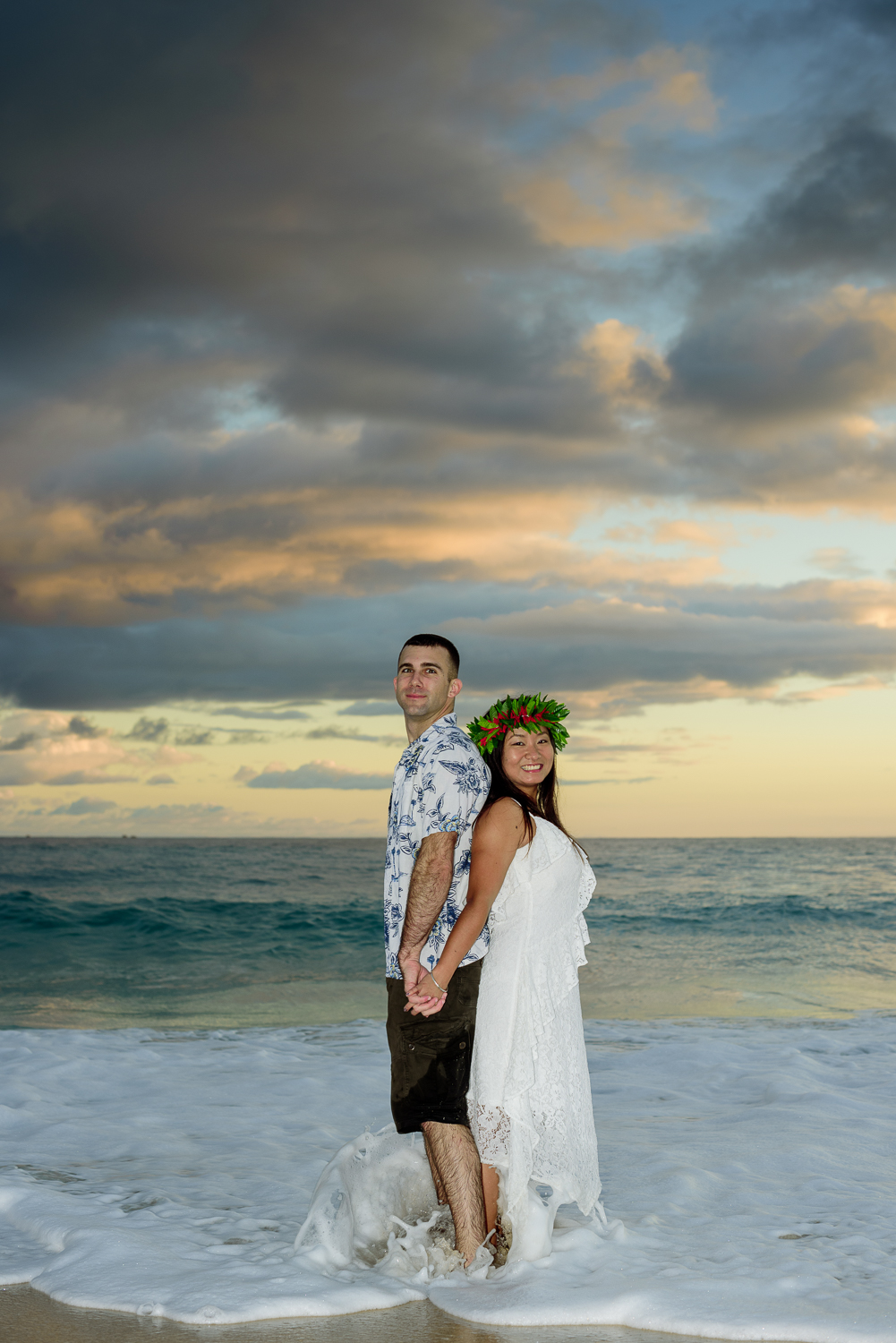 Couple posing back to back in front of Kaneohe beach