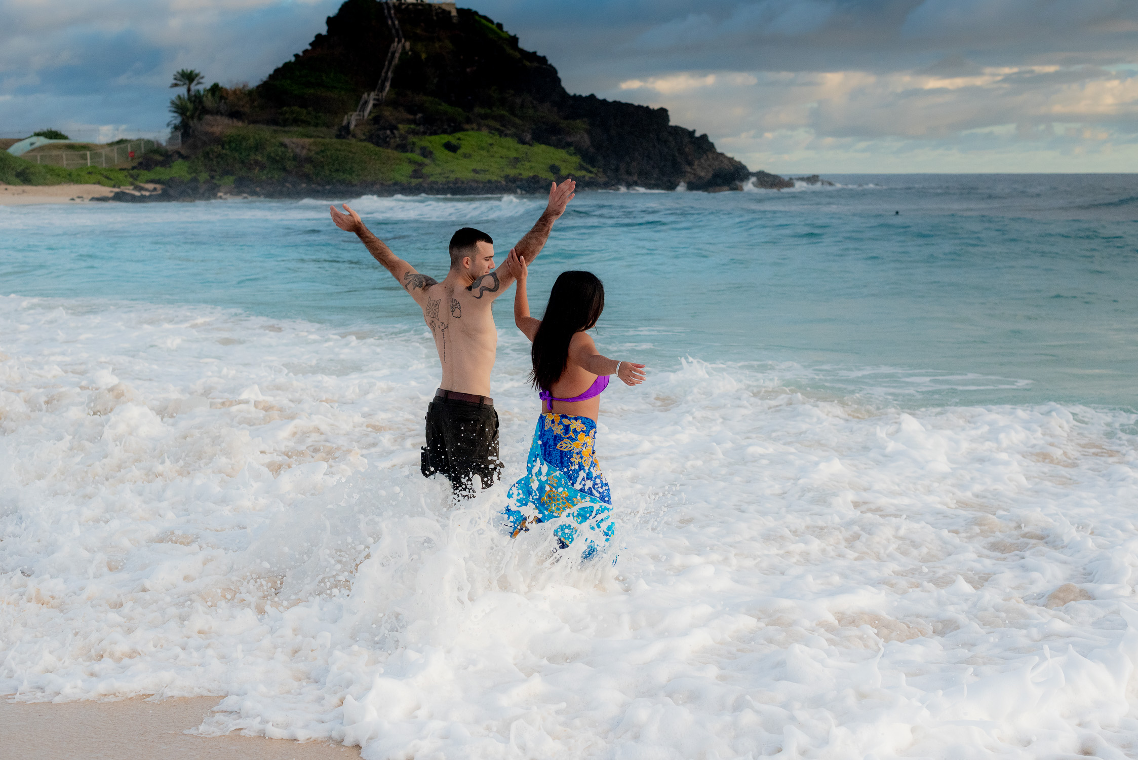 Couple spashing at waves at Kaneohe beach