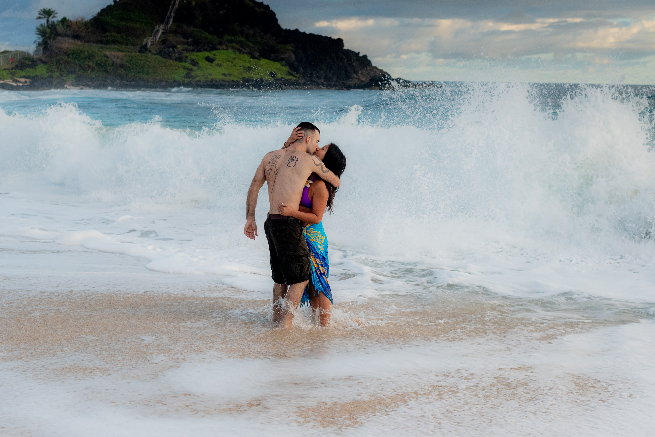 Couple kissing in the surfbreak