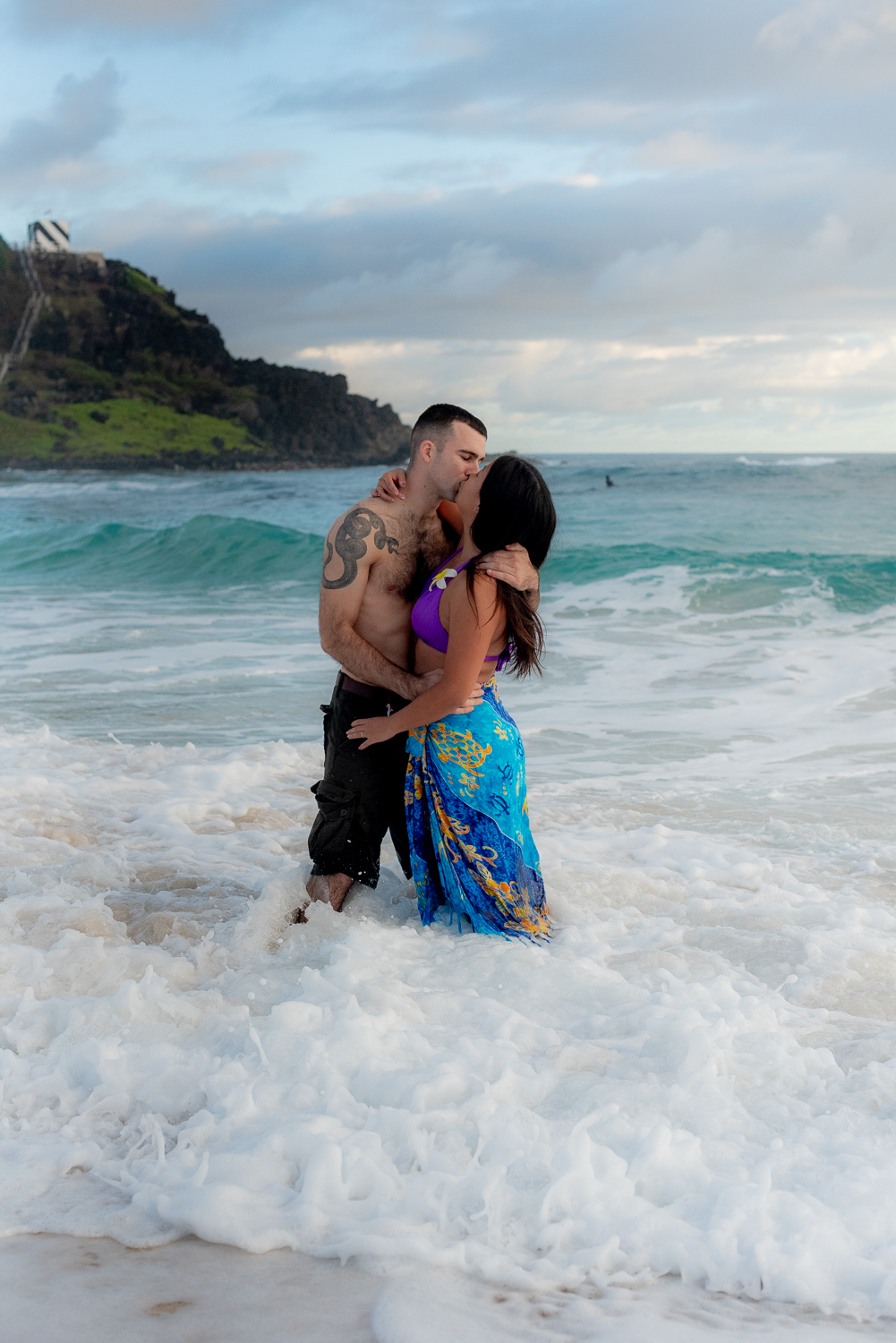 Couple kissing in waves at Kaneohe beach