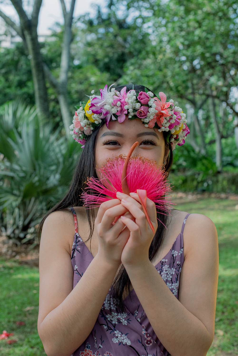 Holding exotic pink flower at Botanical Garden, Oahu