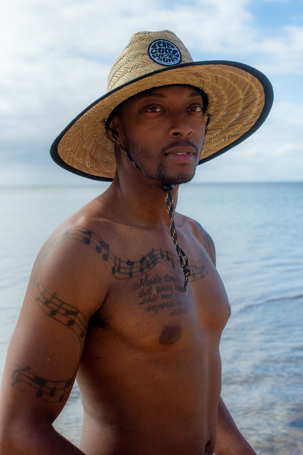 Headshot of shirtless guy with tattoos and beach hat