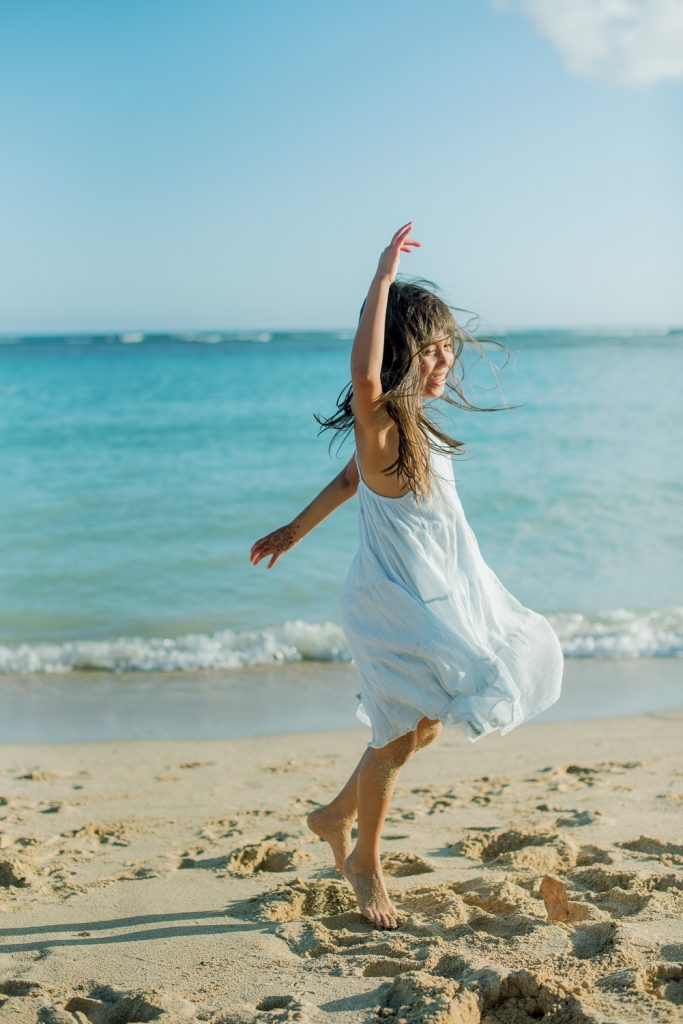 Girl in dress jumping at Ala Moana Beach