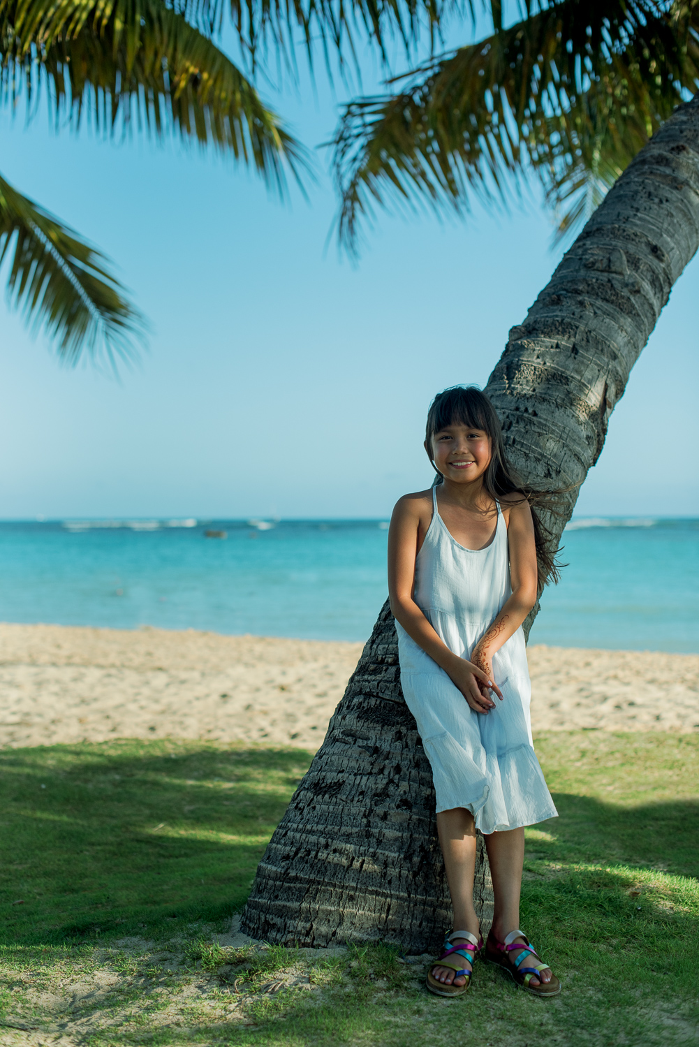 Girl in blue dress in front of coconut tree