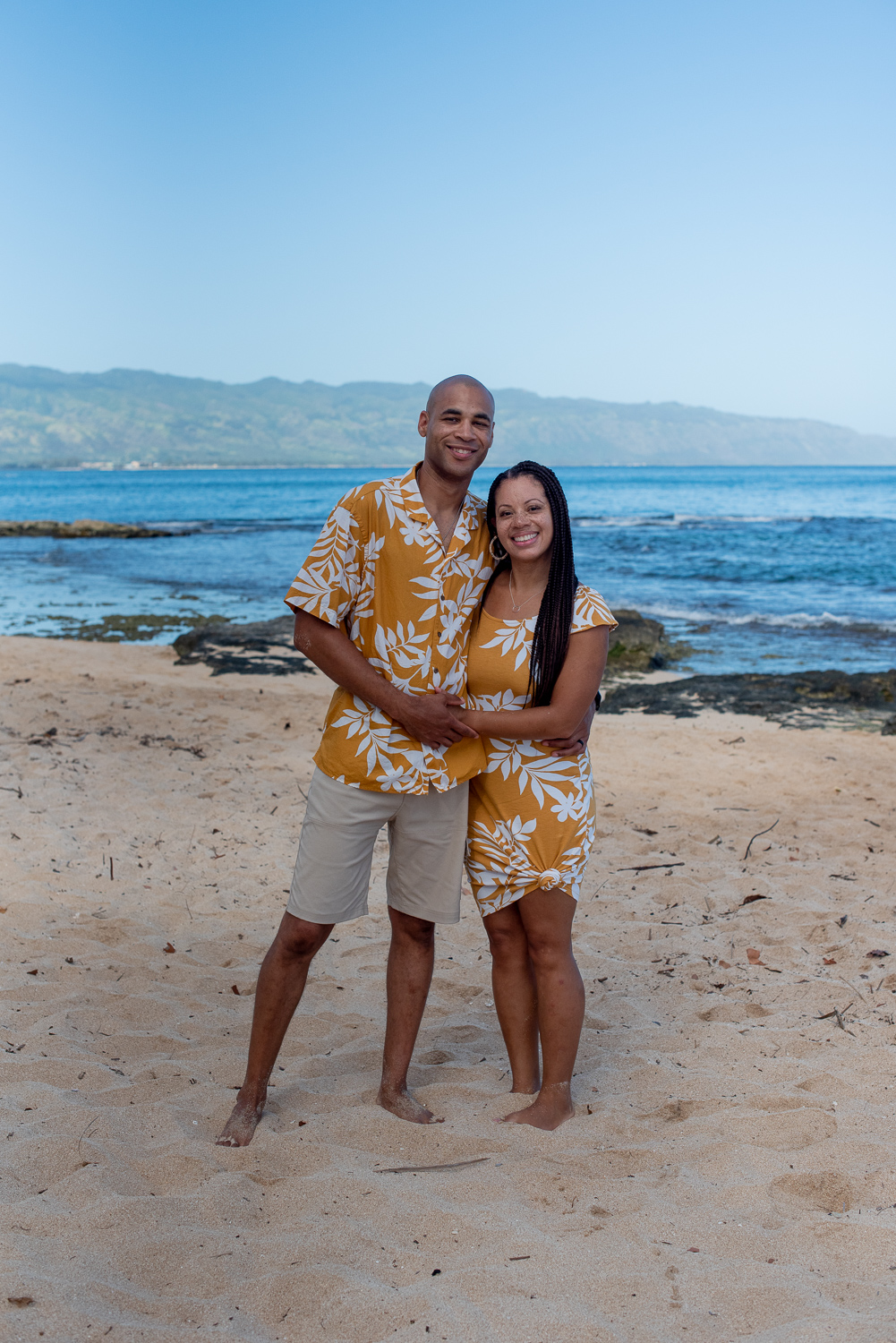 Couple dressed in yellow Hawaiian print at North Shore beach