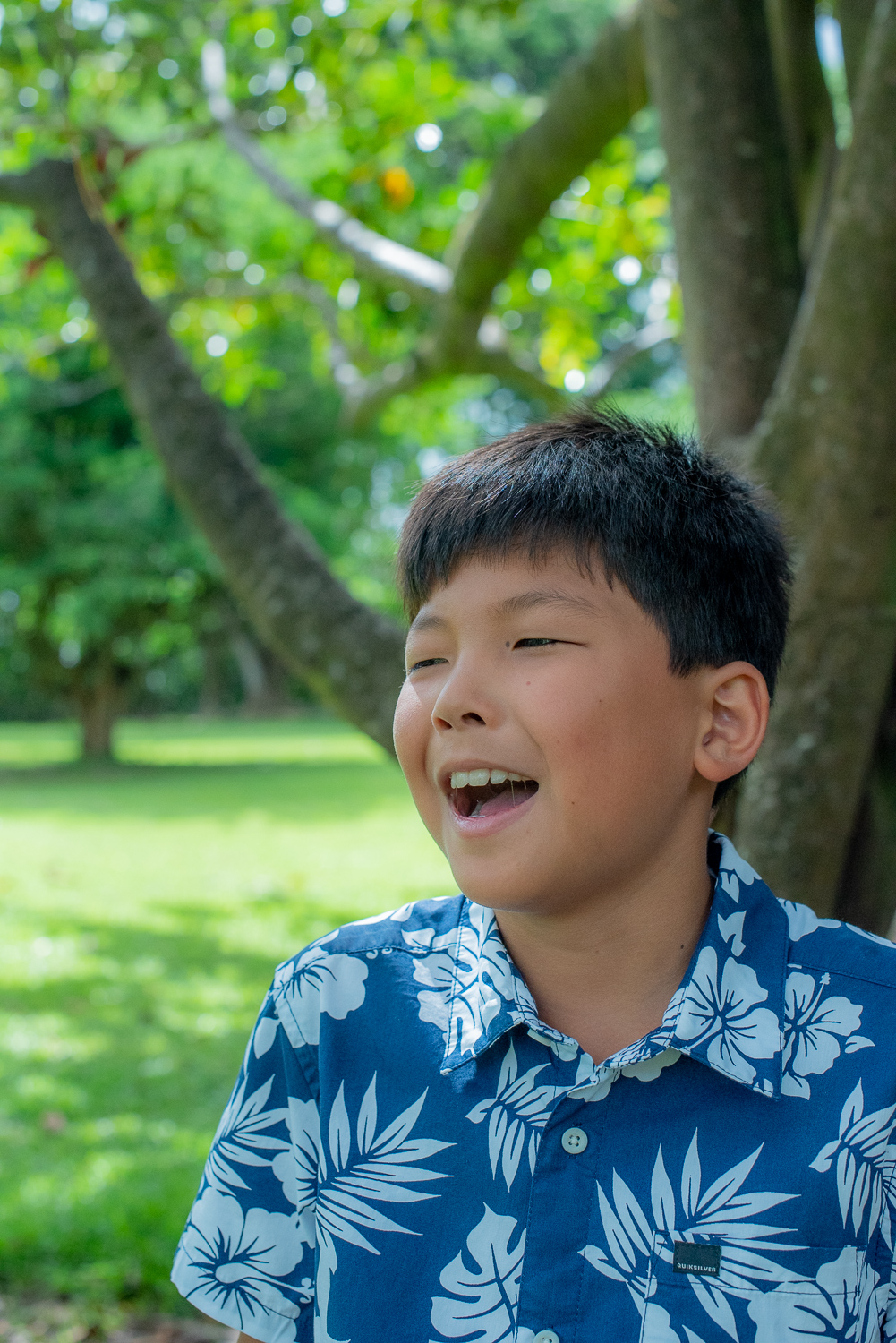 Young man with blue aloha shirt laughing