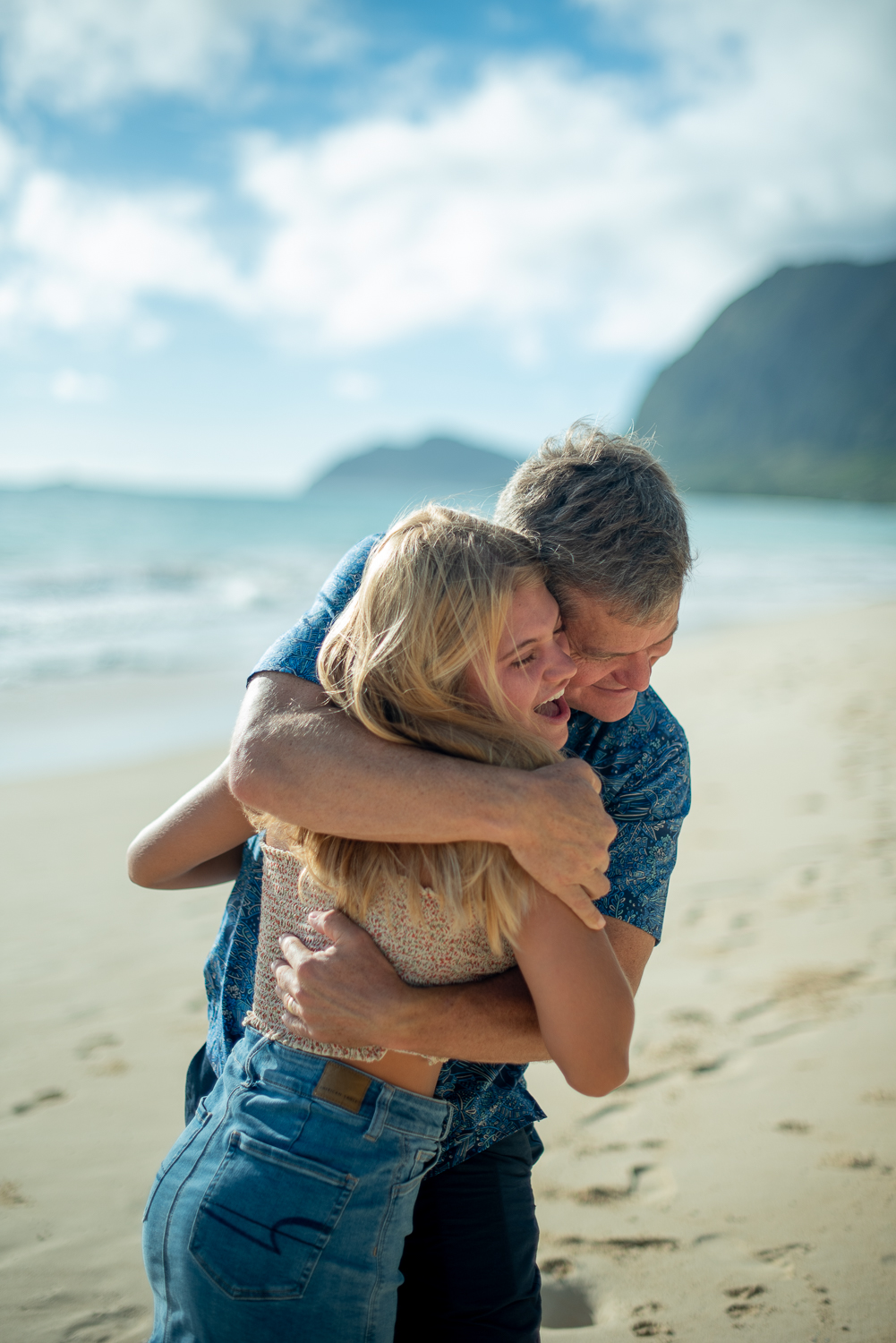 Dad hugging daughter on Waimanalo Beach