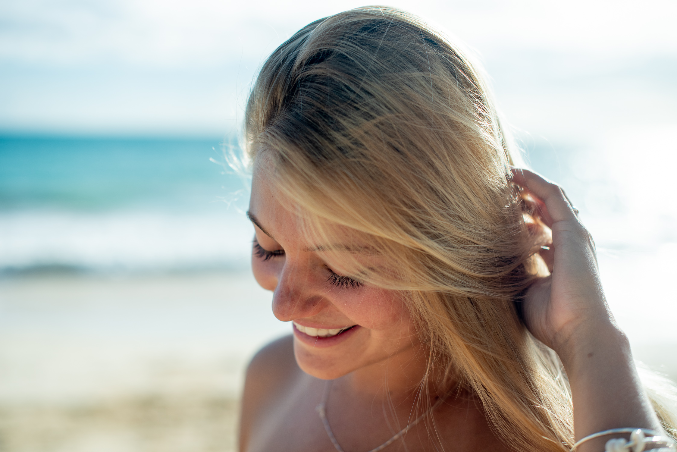 Close up of girl getting hair out of face on beach