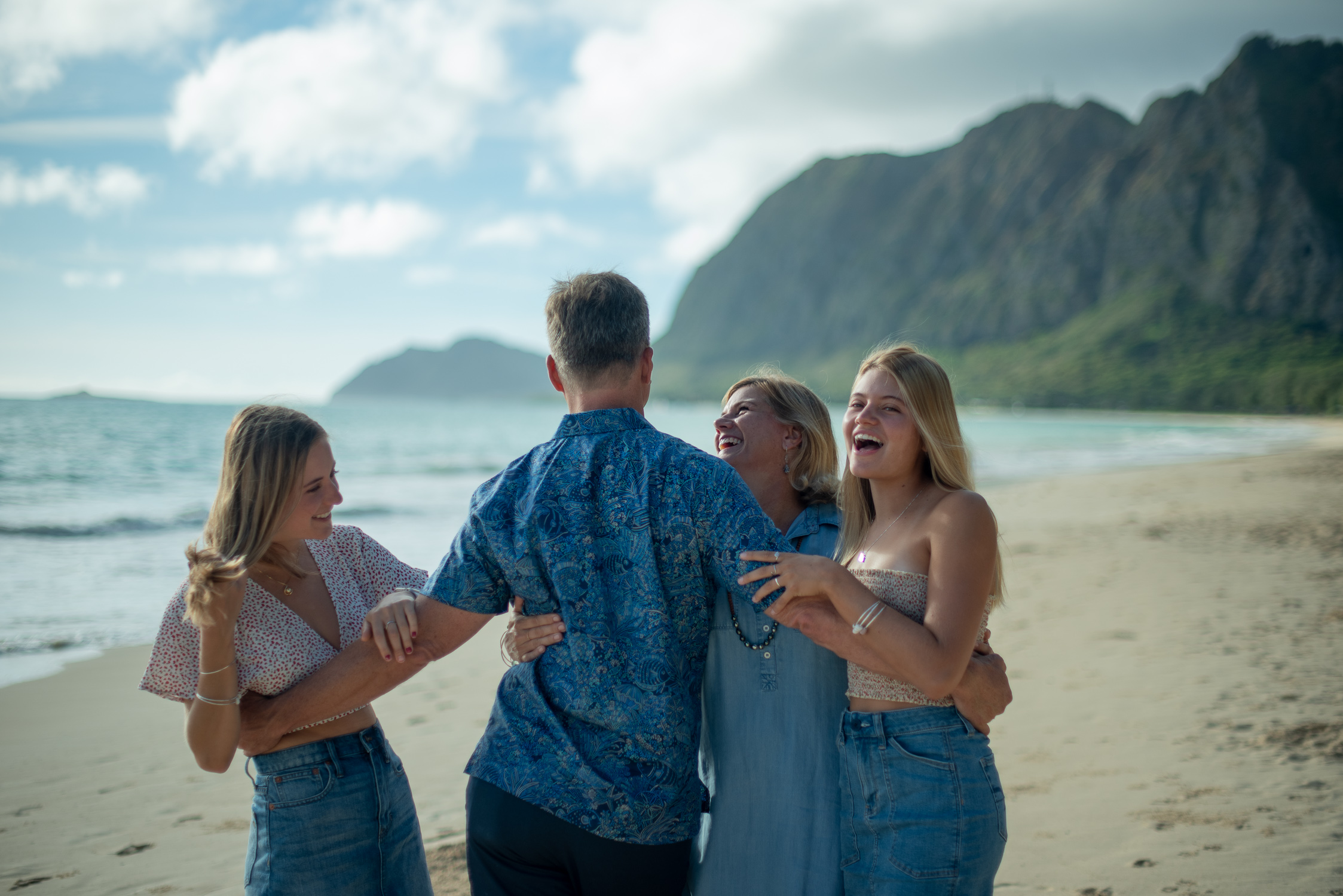 Family of four with back of Dad turned to camera at Waimanalo Beach
