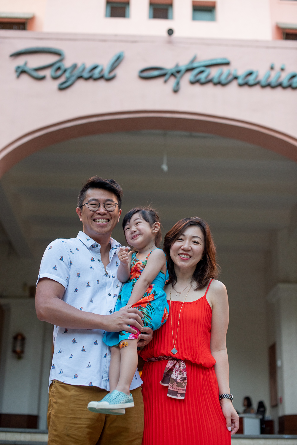 Family of three in front of Royal Hawaiian Sign