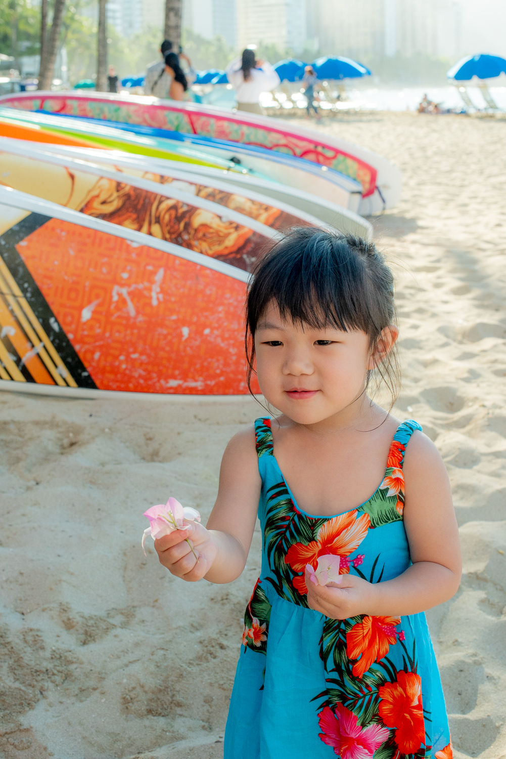 Small girl handing out flowers at beach