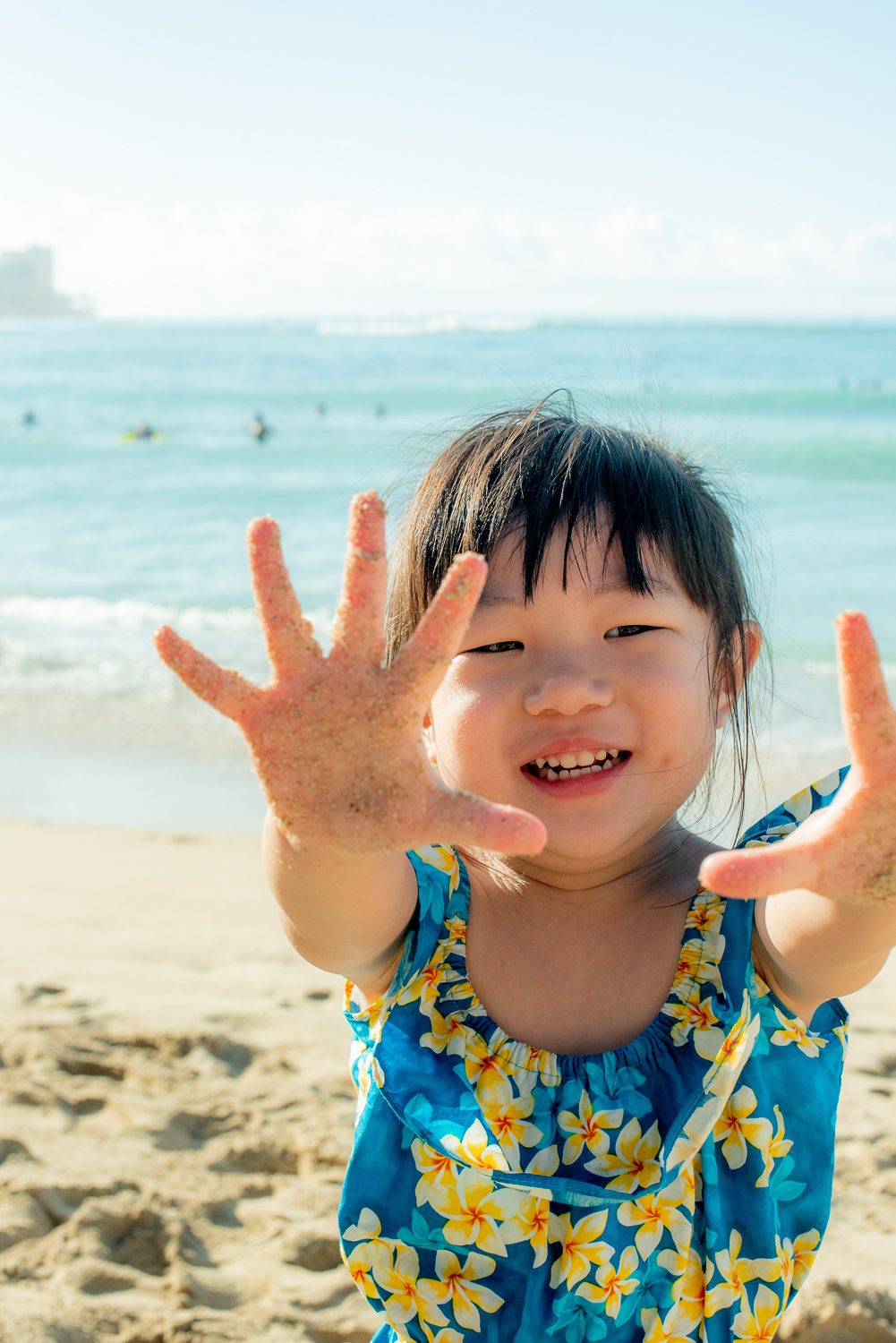 Girl showing off sandy hands at Waikiki Beach