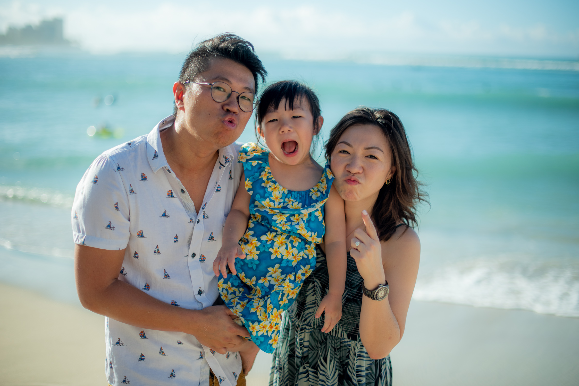 Mom, Dad and daughter making silly faces on Waikiki beach