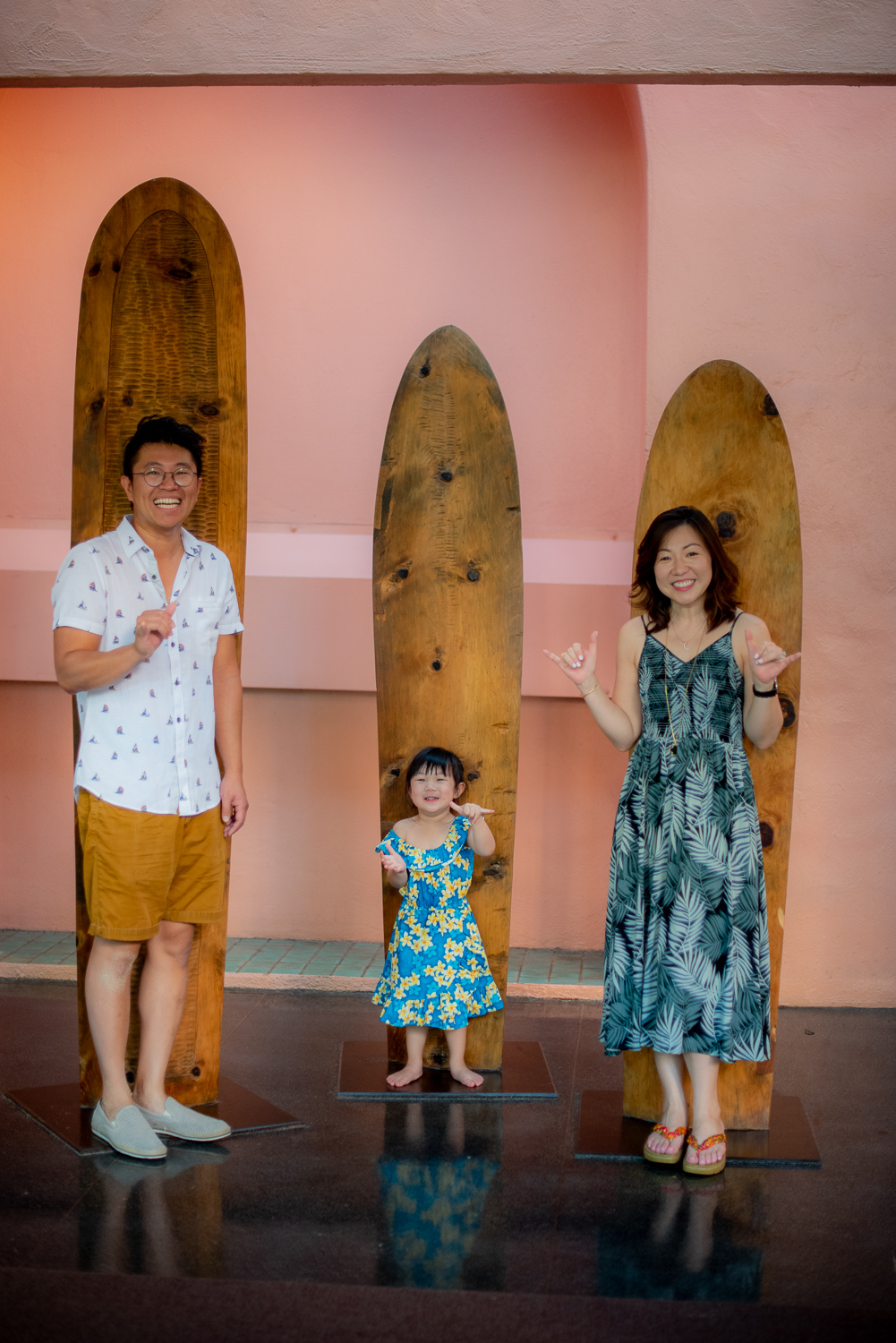 Family standing in front of wooden surfboards at the Royal Hawaiian Hotel