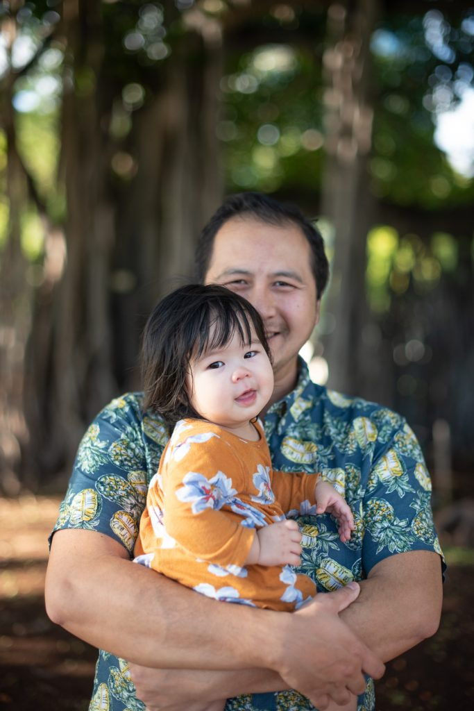 Dad and baby smiling in front of Banyan tree at Ala Moana Beach Park