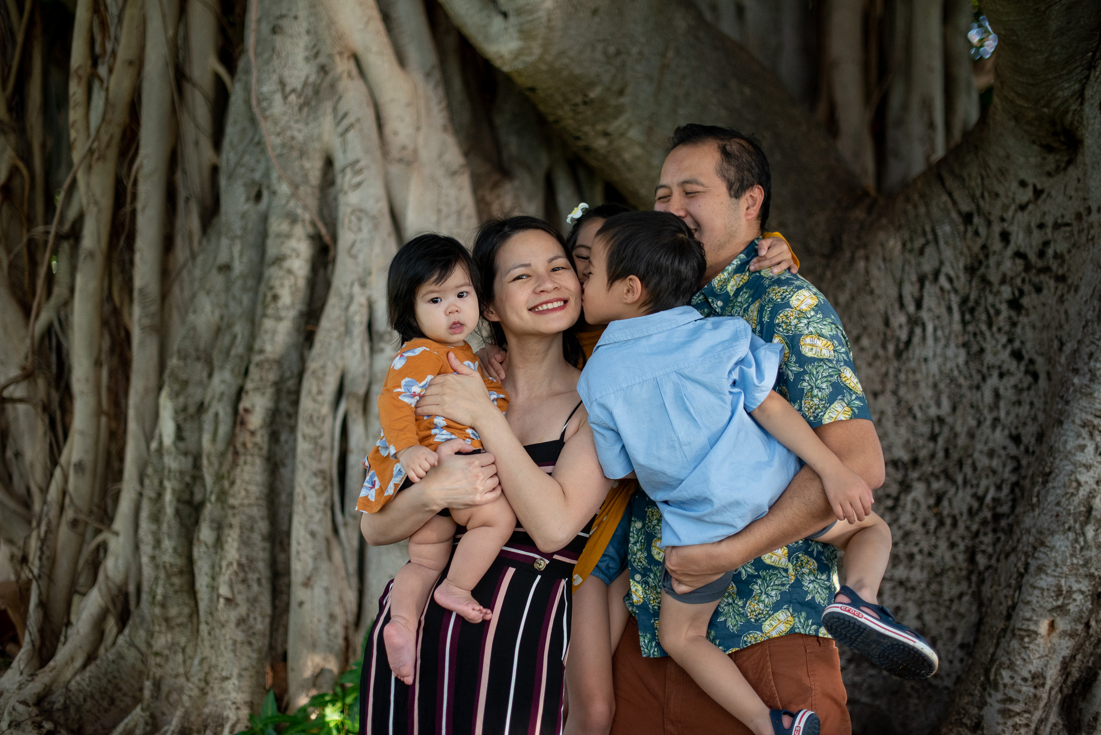 Family kissing mom in front of banyan tree at Ala Moana Beach Park
