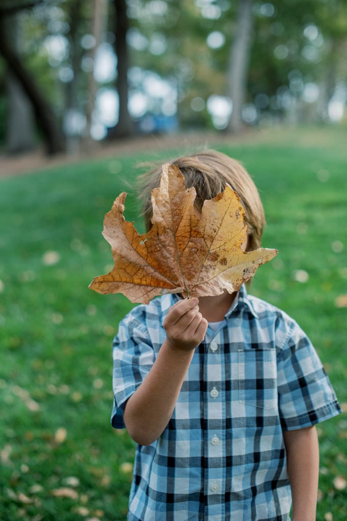 Boy with leaf in front of face