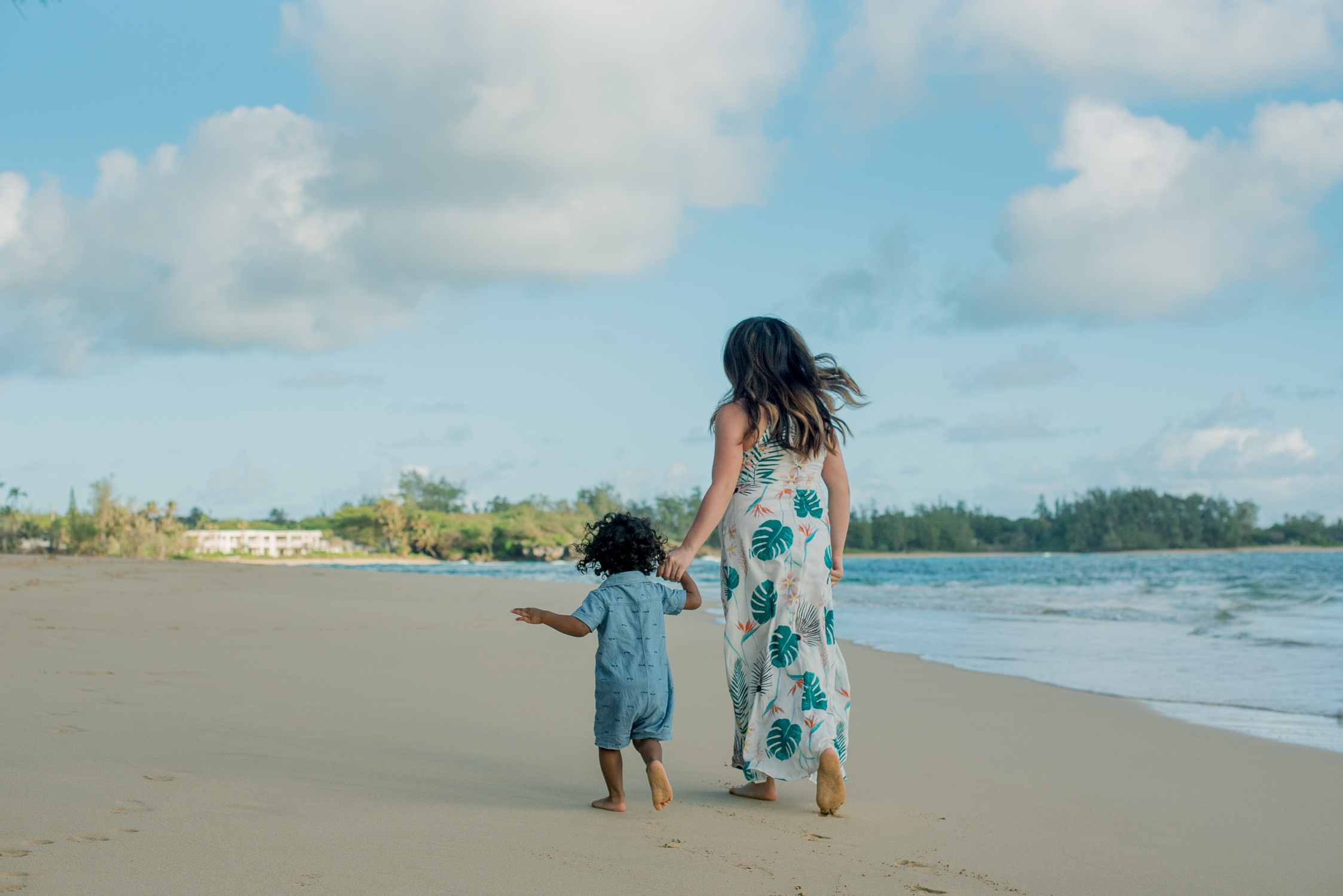 Mom and son walking along empty Laie Beach