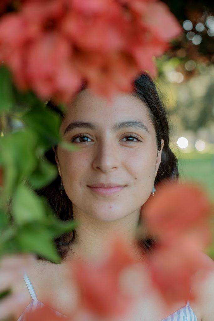 Close up of College Senior with orange bouganvilla framing her face